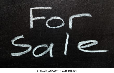A For Sale sign, written on a black board with chalk.