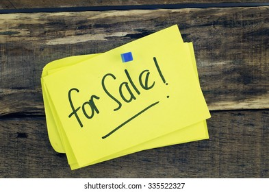 for sale sign written on yellow paper. dark wood texture background