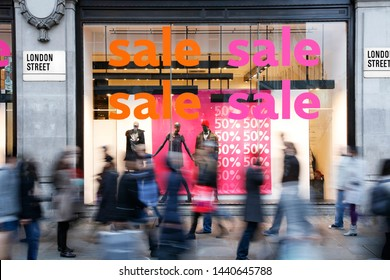 Sale signs in shop window at London's shopping street, motion blurred people present