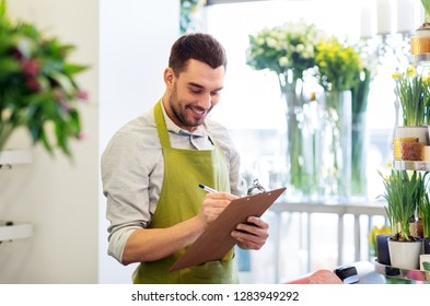sale, small business and floristry concept - happy smiling florist man writing to clipboard at flower shop counter