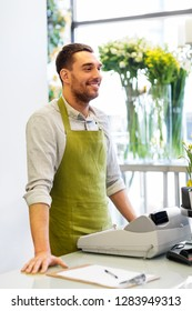 sale, small business and floristry concept - happy smiling florist man with cashbox standing at flower shop counter