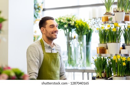 sale, small business and floristry concept - happy smiling florist man or seller at flower shop