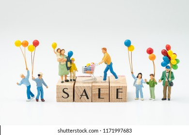 Sale, special offer or end of season concept, miniature people happy family holding balloons with man and shopping cart on top of wooden stamp building word SALE, celebrate discount event.