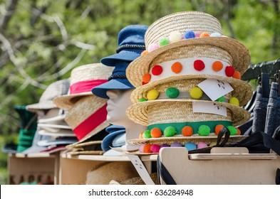 The sale of summer hats. Handmade, season trend - multicolored pom-poms on straw hats.