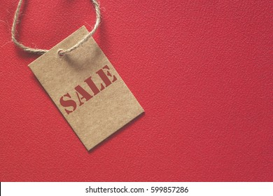 Sale tag made of recycled paper on red background