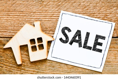 Sale text. Small house with on wooden table.