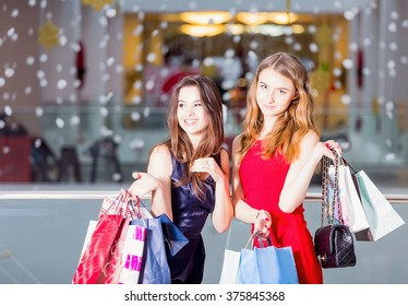 sale, tourism, shopping and happy people concept - two beautiful women with shopping bags in the shopping center.