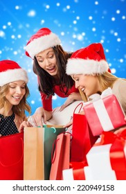 sale, winter holidays, christmas and people concept - smiling young woman in santa helper hat with gifts and shopping bags over blue snowing background