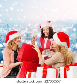 sale, winter holidays, christmas and people concept - smiling young women in santa helper hats with gifts and shopping bags over snowy city background