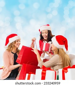 sale, winter holidays, christmas and people concept - smiling young woman in santa helper hat with gifts and shopping bags over blue lights background