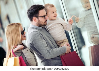 Sale,consumerism and people concept - happy family with little child and shopping bags in city.
