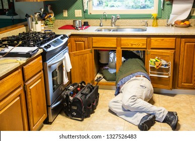 Salem, Oregon - 1/18/2019:  A plumber making repairs to a garbage disposal and instant hot water appliance, under a kitchen sink where there was little room fot a big guy to work