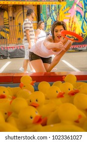 Salem, Oregon - 9/1/2008:  Young woman throwing ring in duck game at the Oregon State  Fair.