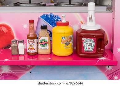 Salem, Oregon - July 8, 2017: Condiments, ketchup, mustard, hot sauce, salt and pepper at food stand at county fair.