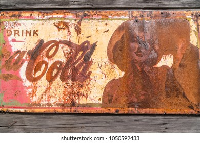 Salem, Oregon - March 13, 2018: Vintage old, rusty Coca Cola drink sign on wooden wall.