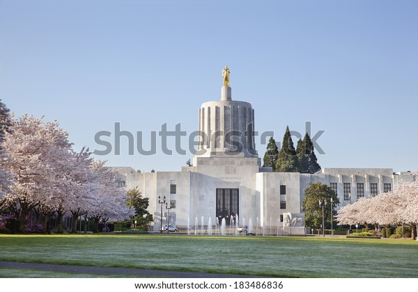 SALEM, OREGON - MARCH 23, 2014: Capitol State Building against a blue sky. Cherry Blossom Trees Blooming at Oregon State Capitol State Park in Salem Oregon during springtime. A tourist attraction.