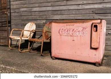 Salem Oregon - March14, 2018: Vintage Old Faded Coca Cola Ice Vending Machine and Rusted Metal Chairs at Old Gas Station in Salem Oregon.