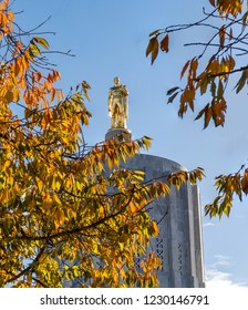 Salem, Oregon - November 3, 2018: Gold Pioneer Statue atop Salem Oregon state capitol building and Autumn Colored Trees blooming in the park.