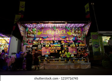Salem, Oregon / USA - August 28, 2018: An isolated point of view of people playing at the Lucky Duck game concession at night -Oregon State Fair