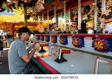 Salem, Oregon USA - July 9, 2021: A man playing at a game concession at the Marion County fair