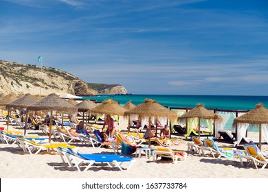SALEMA, PORTUGAL-SEPT. 23: Tourists are seen sunbathing on the beach Salema, Portugal in The Algarve with cliffs in distance on September 23, 2019.