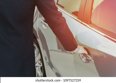 Salemans hand on handle opening a car door with sunlight in matte