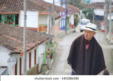 Salento, Colombia - March. 2019: The people of Colombia, an old man walking in the colorful streets of Salento Village.