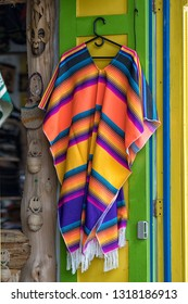 Salento, Colombia - September 7, 2018: colourful poncho on hanger displayed on the door of a souvenir shop