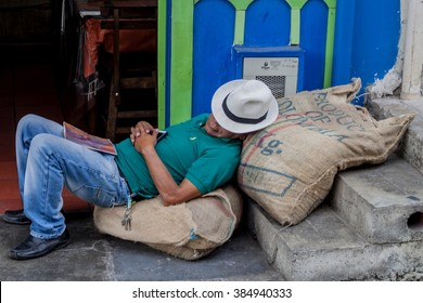 SALENTO, COLOMBIA - SEPTEMBER 8, 2015: Worker sleeps on bags of colombian coffee.