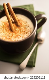 Salep with cinnamon in brown cup on white table