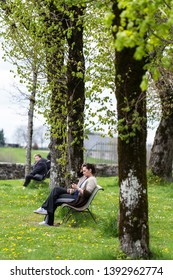SALERS, FRANCE - APRIL 16, 2017: A woman consults her smartphone sitting on a bench, in a village park.