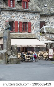 SALERS, FRANCE - APRIL 16, 2017: Tourists sat on the terrace of a coffee shop in the medieval historical center of the village.
