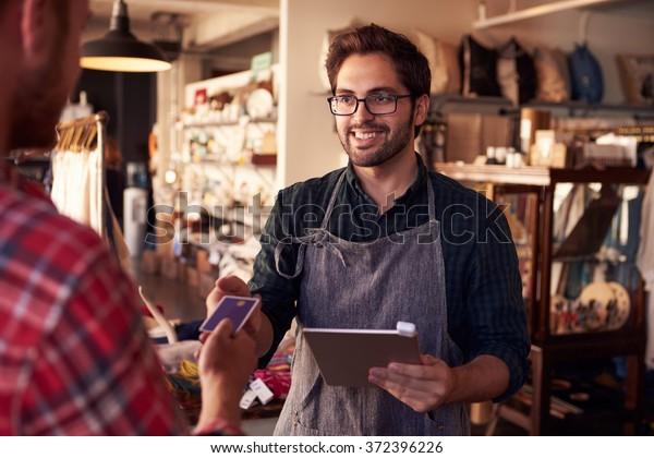 Sales Assistant With Credit Card Reader On Digital Tablet