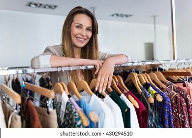 Sales assistant leaning on a clothing rail