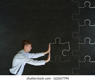 Sales businessman pushing chalk jigsaw puzzle piece into place on blackboard background