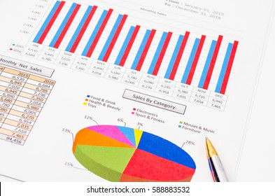 Sales by category and graph report document with pen.