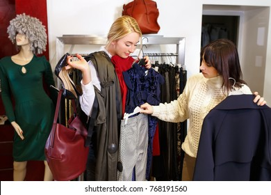 sales consultant helping chooses clothes for the customer in the store. Shopping with stylist. Beautiful female shop assistant consulting young woman in the fashion boutique