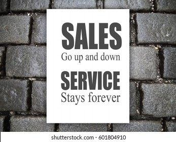 Sales go up and down, Service stays forever. Background of cobbles, on white paper, gray letters. Motivation, poster, quote, blurred image