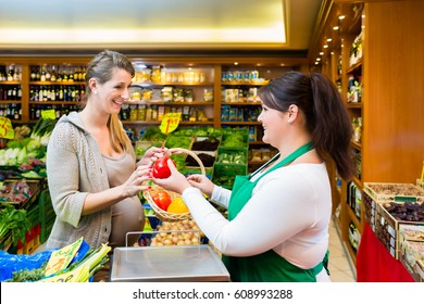 Sales lady handing vegetables to woman in grocer store