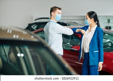 Sales manager and customer in medical masks doing elbow bump when greeting each other in car dealership
