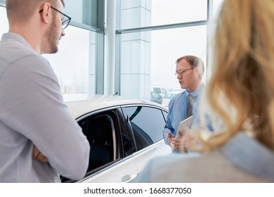 Sales manager helping young couple choose a new car