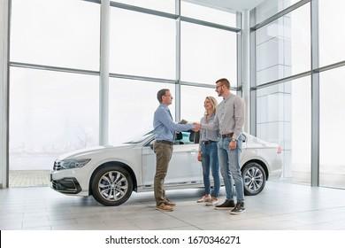Vertriebsleiter, der jungen Paaren hilft, ein neues Auto zu wählen und nach einem erfolgreichen Kauf eines Autos im modernen Autosalon die Hände zu schütteln
