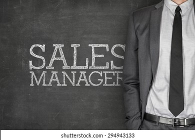 Sales manager on blackboard with businessman on side