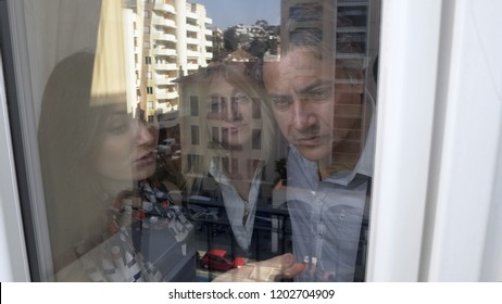 Sales manager showing customers view from window, reflection of city in glass