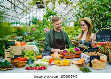 Sales people young man and woman are talking during organic food sale in greenhouse, fresh fruit and vegetables visible on table. Business and healthy nutrition concept.