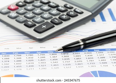 Sales report analysis with pen, and calculator
