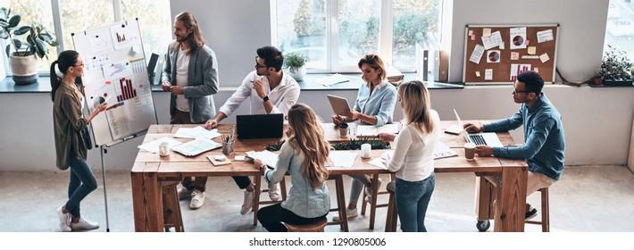 Informe de ventas. Vista superior de dos jóvenes colegas modernos que realizan una presentación de negocios mientras están en la sala de juntas