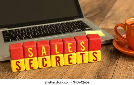 Sales Secrets written on a wooden cube in a office desk