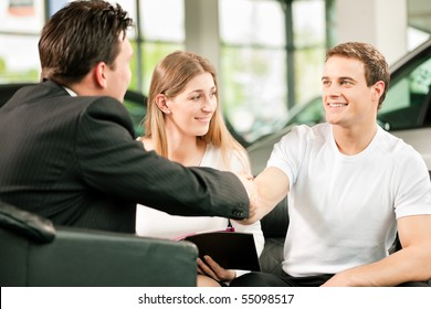 Sales situation in a car dealership, the dealer is shaking hands with a young couple, they want the car in the background