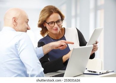 Sales team discussing new project while sitting at desk at office.